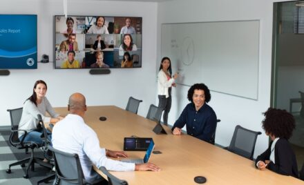 Image for: Two males and three females collaborating in a conference room featuring an HP Teams Meeting Rooms touch display. The meeting has nine remote participants shown on a wall mounted display joined via Teams Meetings. Two subjects are using Surface devices.