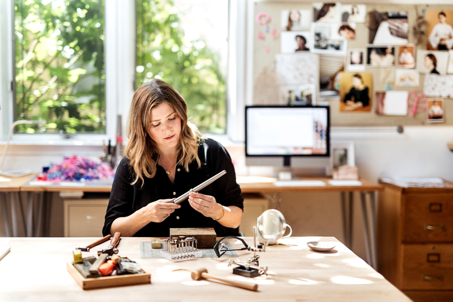 Image shows Jennifer Sarkilahti in her workplace creating one of her unique pieces.