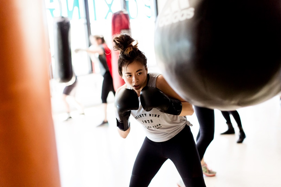 Lynn Le, Society Nine founder, uses a boxing bag while wearing her combat sports gear.