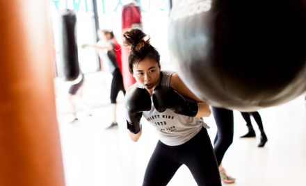 Image for: Lynn Le, Society Nine founder, uses a boxing bag while wearing her combat sports gear.