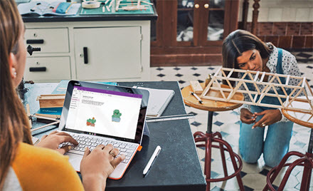 Two students work on a school project, a small wooden bridge. One works out of OneNote, the other on the bridge.