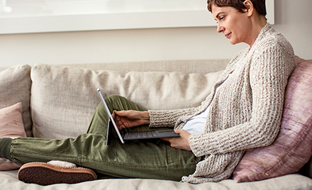 A woman sits on her couch with an open laptop.