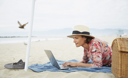 A woman works remotely under a parasol, laptop open on a beach towel.