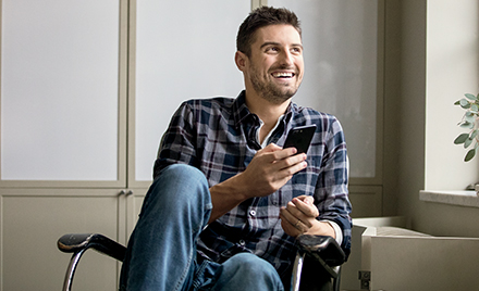 A man sits back in his chair, smiling and holding a smartphone.