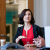 Image of a woman in a meeting, gesticulating as she speaks.