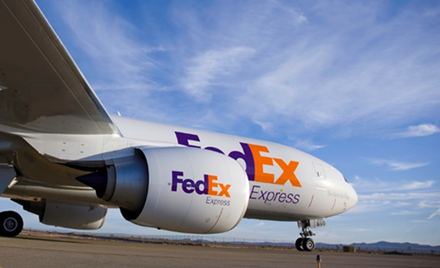 Image for: A FedEx plane sits on a runway preparing for takeoff.