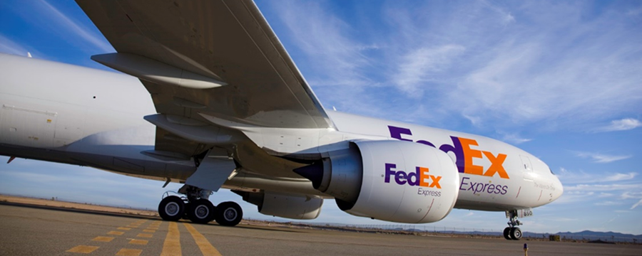 A FedEx plane sits on a runway preparing for takeoff.