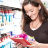 Image of a woman in a supermarket aisle holding a Henkel product.