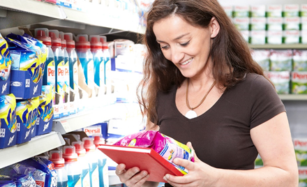 Image for: Image of a woman in a supermarket aisle holding a Henkel product.