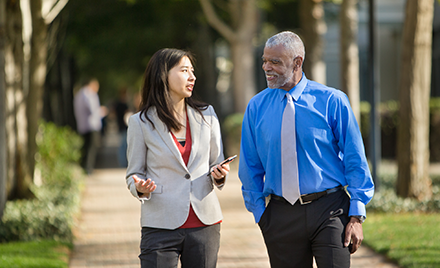Image for: Image of two employees walking along a sidewalk discussing something over a mobile device.
