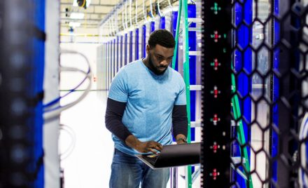 IT pro standing in a data center working on a PC