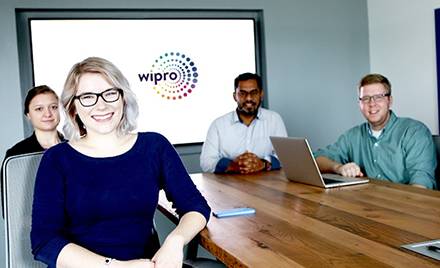 Image of a group of Wipro employees sitting around a conference table.