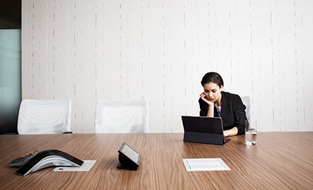 Image of a worker at a conference table working on her tablet.