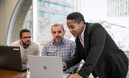 Image of a team of three collaborating over a computer.