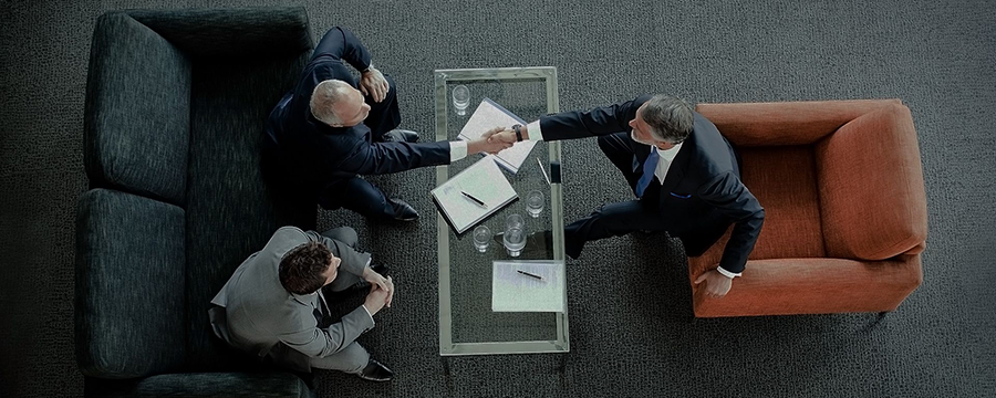 Three workers sit around a conference table. Two shake hands.
