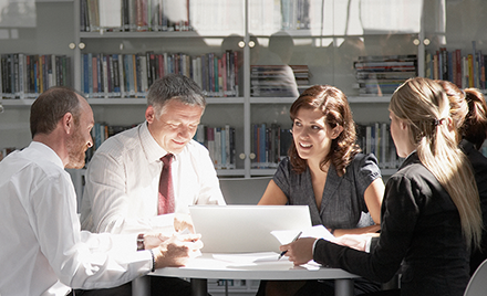 Image of five Korn Ferry employees meeting around a desk.
