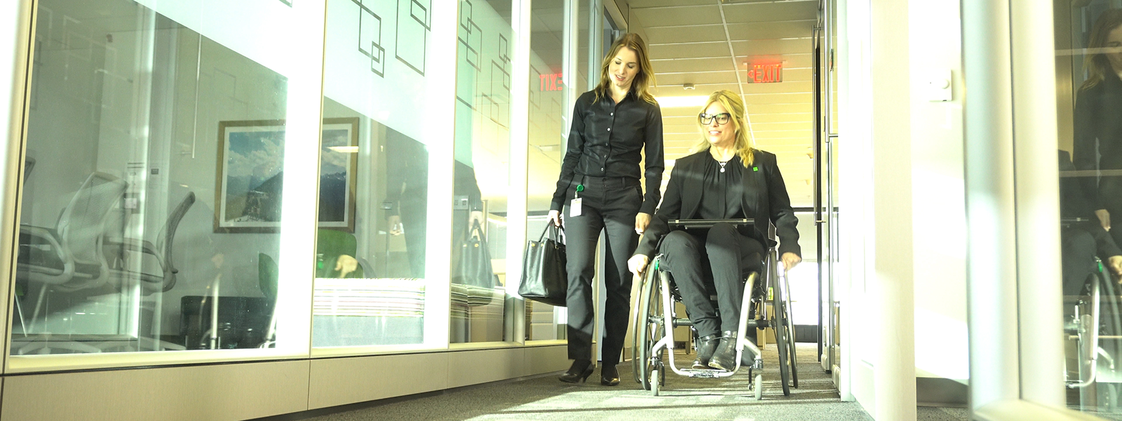 Image of two workers chatting in an accessible workplace hallway, one standing, the other from a wheelchair.