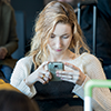 Image of a woman in an airport working on her phone.