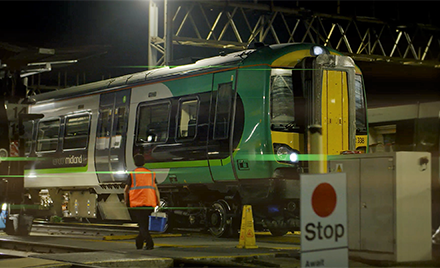 A firstline worker stands on a train platform of London Midland while a train pulls in.