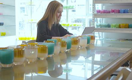 Image of a firstline worker at glassybaby. She is typing on a laptop amid a lineup of glassybaby votives.