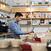 Image of a bakery owner and operator working on his laptop amid bowls and coffee cups.