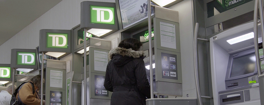 Image of customers standing at a row of TD Bank ATMs.