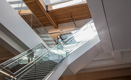 Image of a worker descending a staircase while looking at her phone.