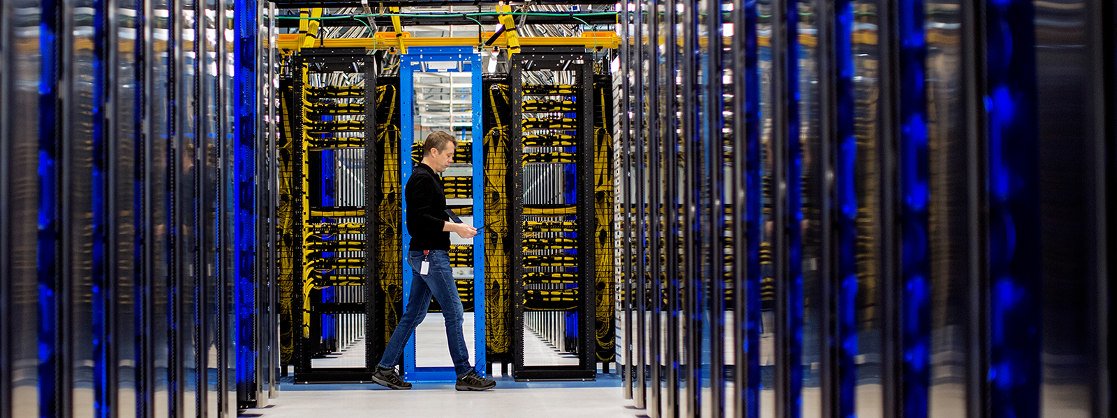 Image of a worker walking amidst servers.