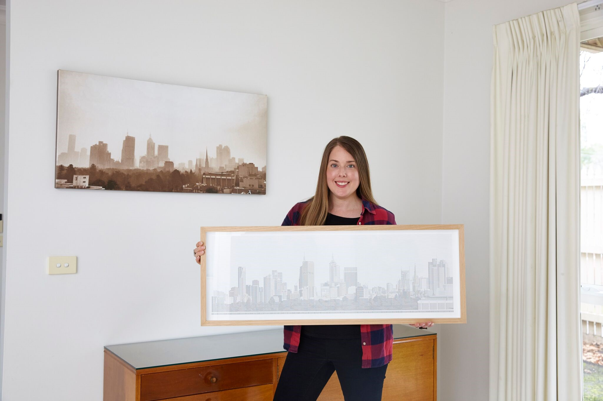 Image of Emma Stevens holding up a Spreadsheet Skyline, made using Excel.