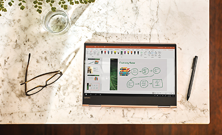 A tablet sits on a desktop with PowerPoint displayed on its screen. A pen sits next to it.