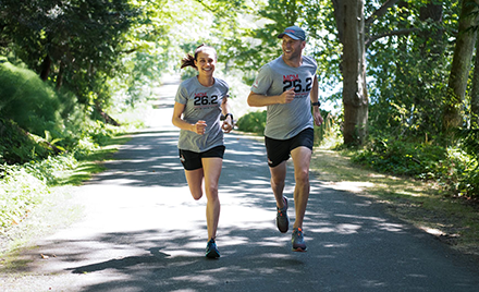 Image of two runners jogging down a forested road.