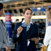 Image of a Firstline Worker in an airport speaking with two passengers.