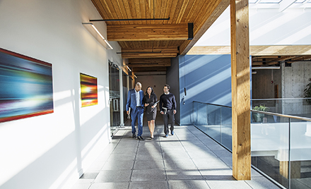 Image of three coworkers walking along a hallway.