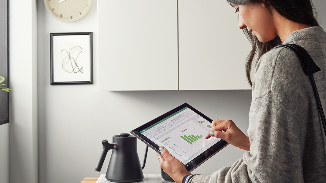 Image of a woman looking at an Excel graph on her tablet.