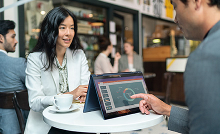 Image for: Image of two workers meeting over a table and an HP Elite Dragonfly.