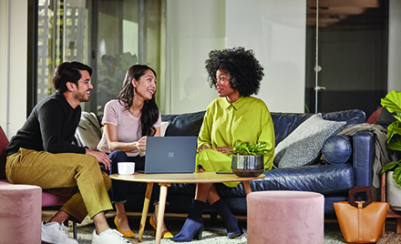Image for: Image of three colleagues chatting on a couch at work.