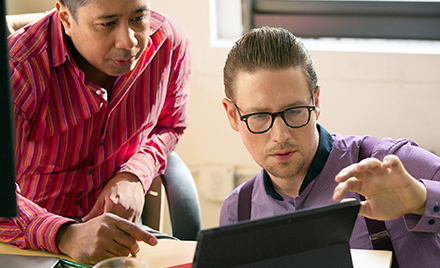 Image for: Two co-workers collaborating on a project on a laptop PC.