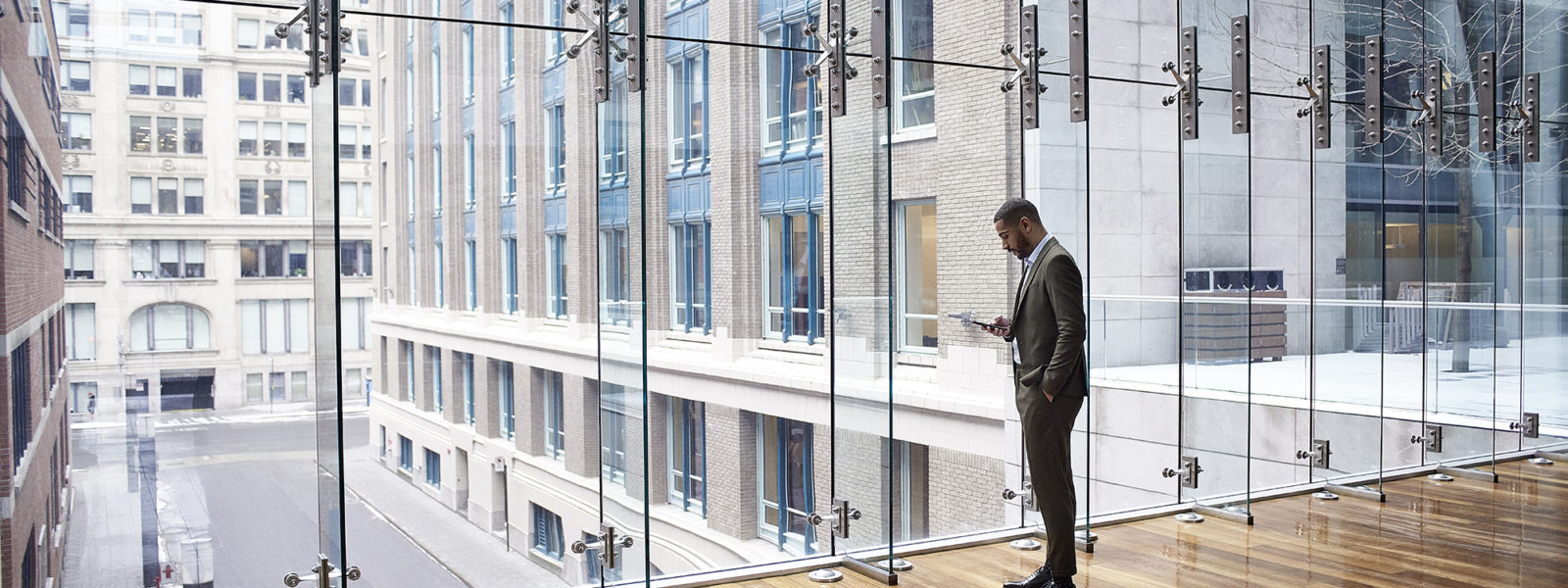 Image of a worker checking his phone while looking out a window over a cityscape.