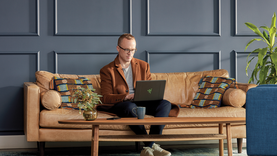 Image of a man working with a laptop PC on a couch.
