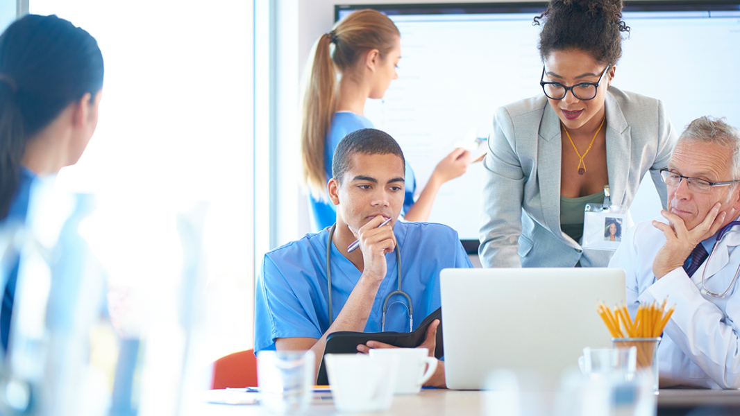 Image of doctors and nurses surrounding a laptop.
