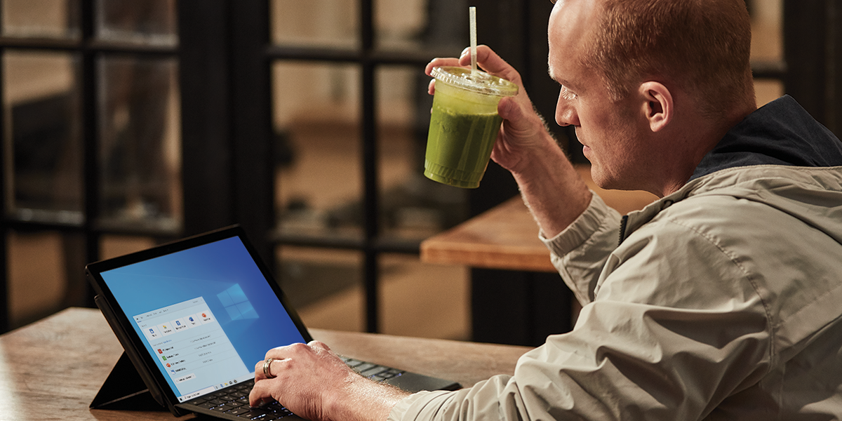 An IT worker holding a smoothie and working on his laptop.