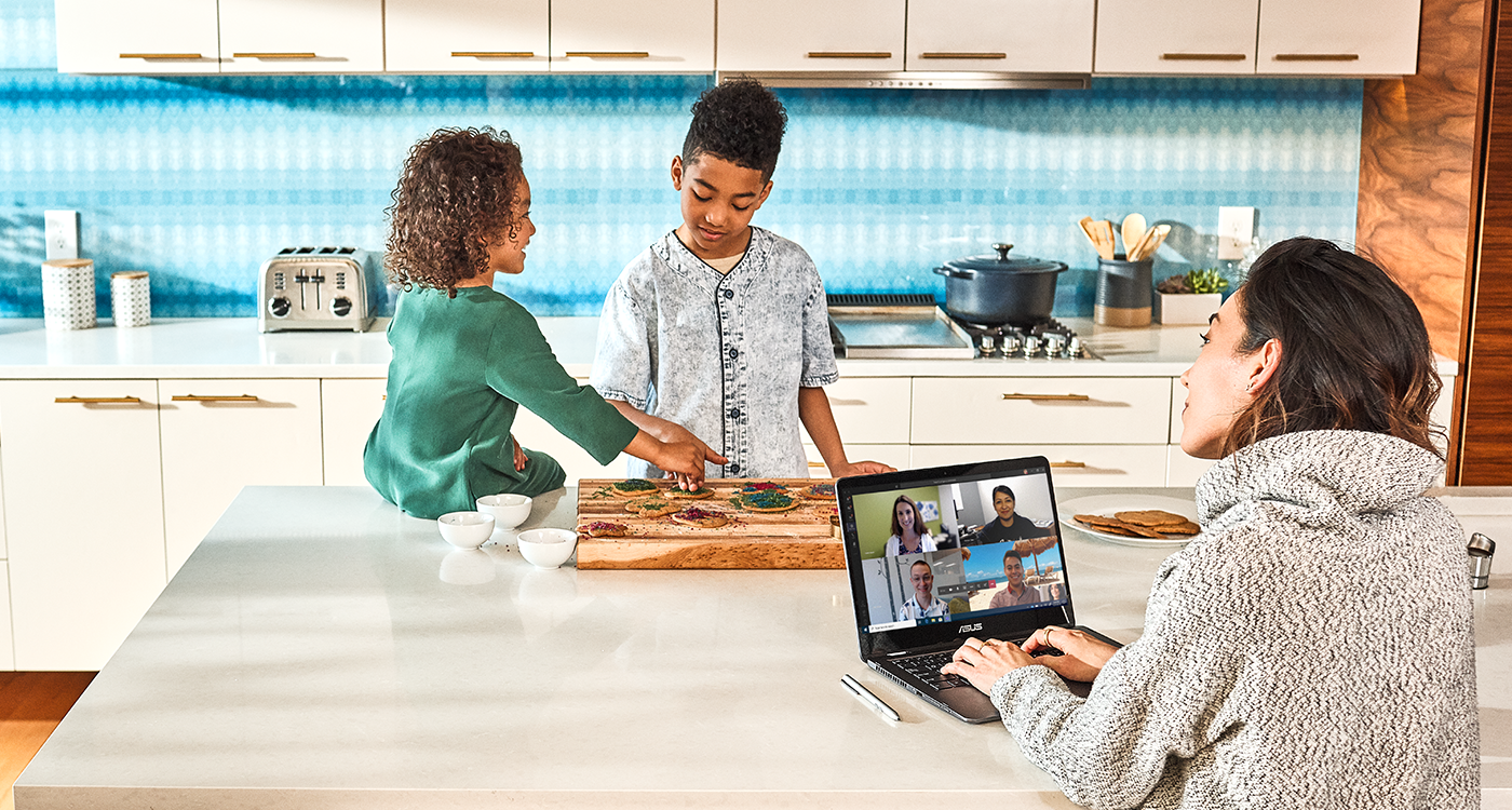 Image of a mother working from home, with her children at the kitchen countertop.