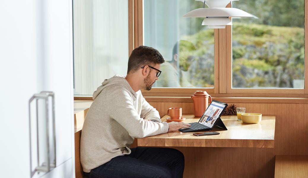 Adult male on the go works from home at breakfast table with Surface Pro 6