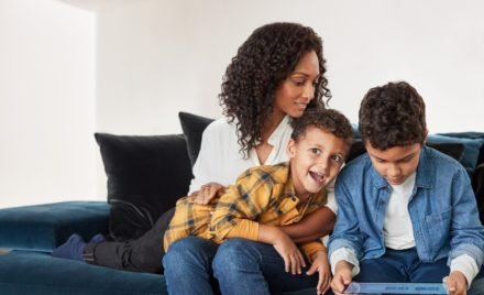 Image for: A family on a couch, one child holding a laptop.