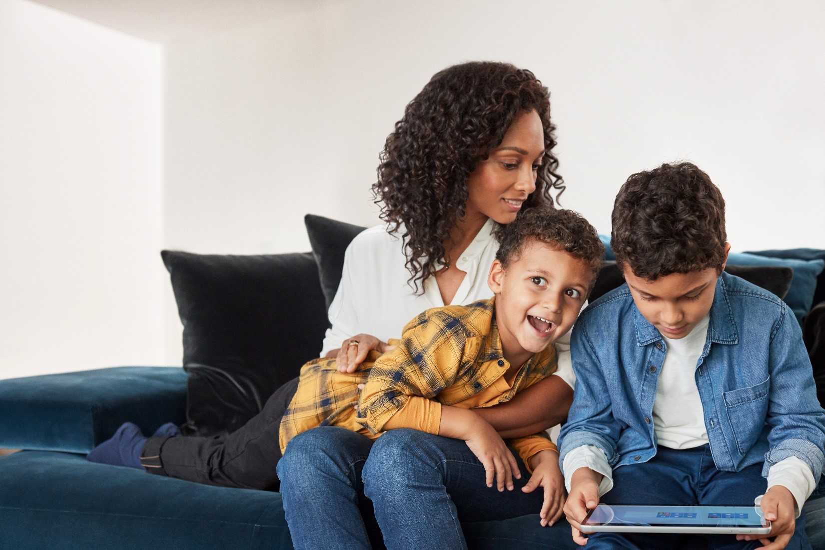 A family on a couch, one child holding a laptop.