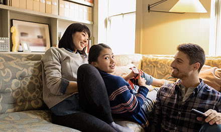 Image for: An image of a family relaxing on a couch using a laptop PC.