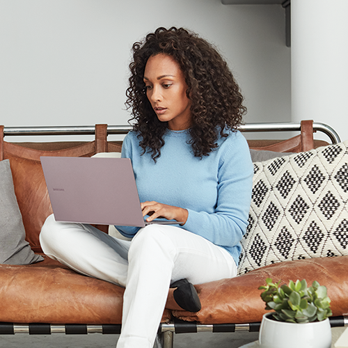 A woman sitting on a couch using her PC laptop.