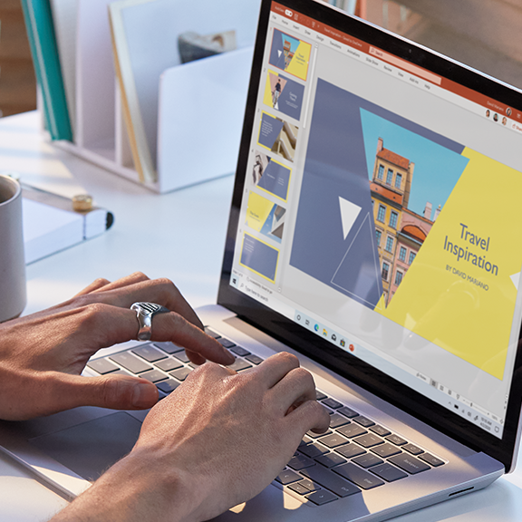 Photograph of worker on Surface Laptop 3 in PowerPoint with Surface Mouse and Surface Headphones.