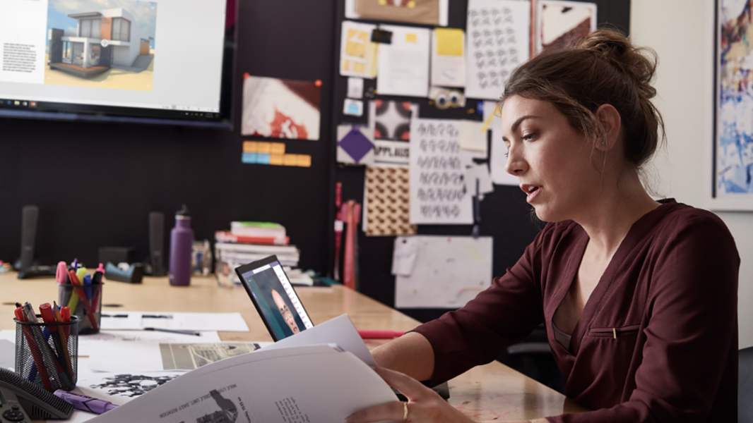 An image of a female small business professional working on designs using devices running PowerPoint and Microsoft Teams.