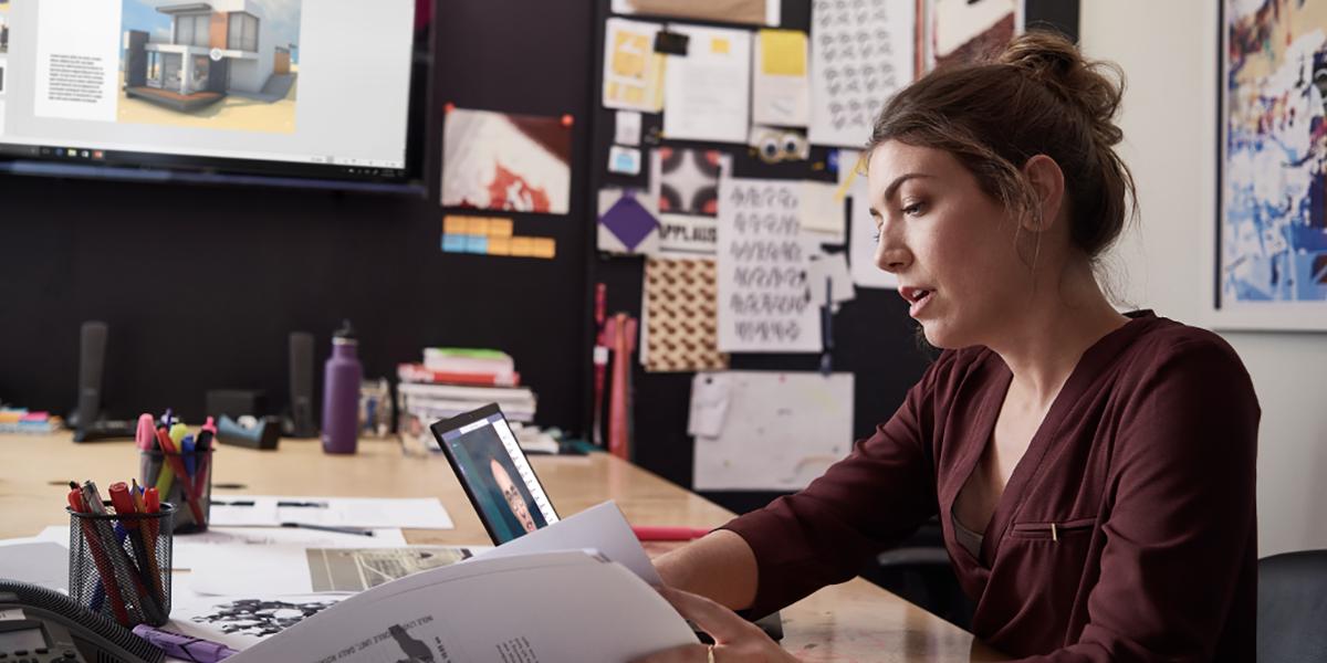 Uma imagem de uma profissional de uma pequena empresa trabalhando em projetos usando dispositivos que executam PowerPoint e Microsoft Teams.